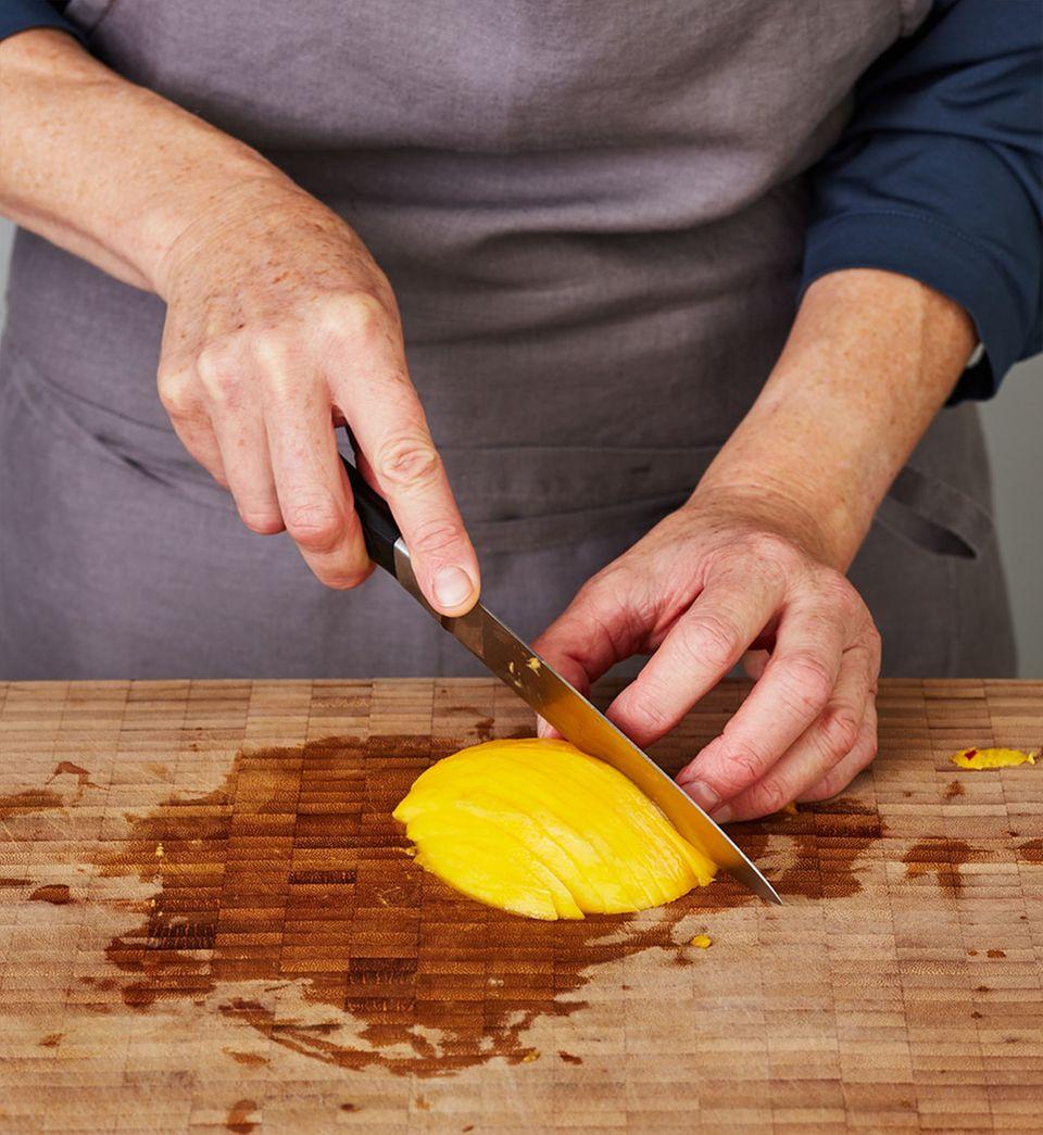 Für die Garnitur eine Mangohälfte mit einem scharfen Küchenmesser längs in dünne Spalten schneiden.
