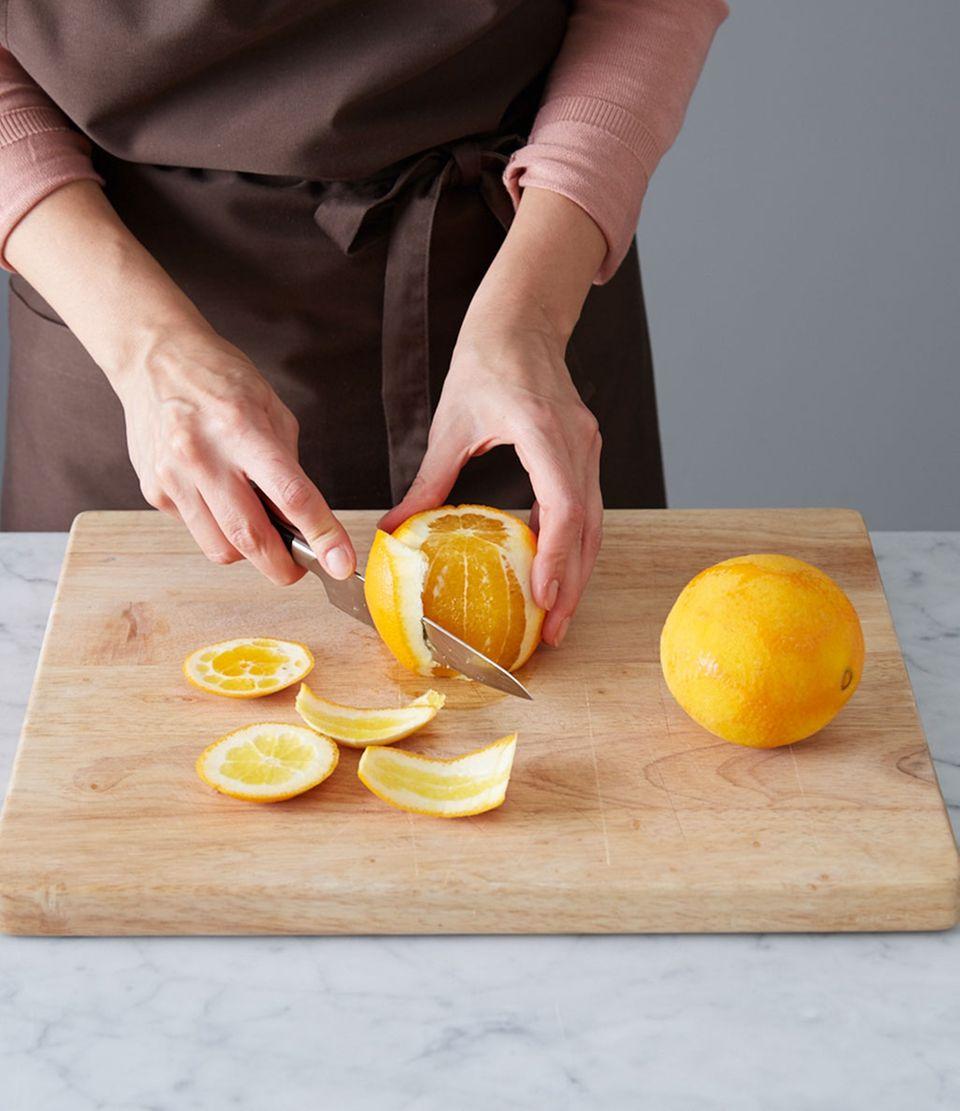 Schale und weiße Haut von den Orangen abschneiden.