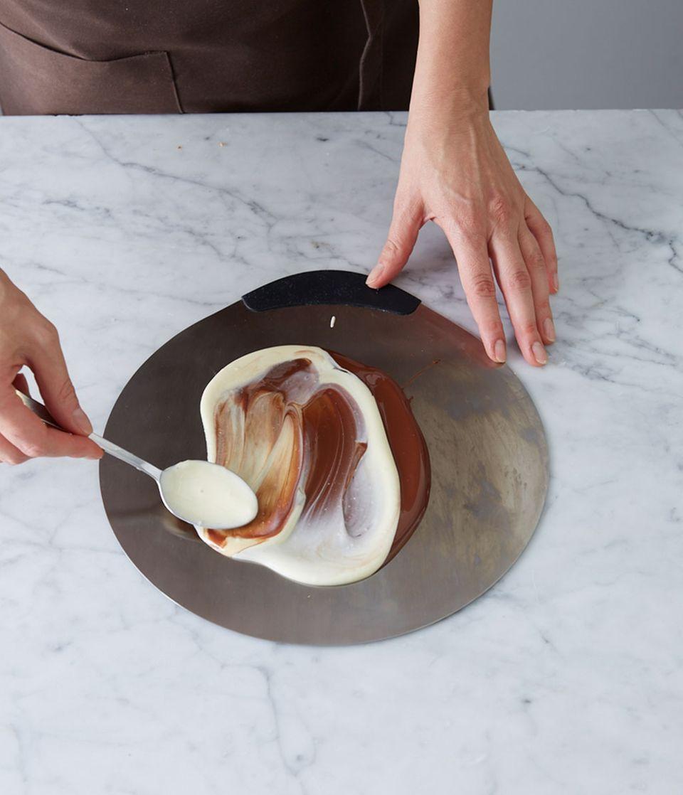 Temperierte Kuvertüren nebeneinander auf einen Tortenretter gießen, mit dem Löffelrücken marmorieren.
