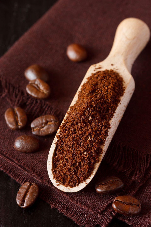 Gemahlener Kaffee auf einem Holzlöffel plus Kaffeebohnen