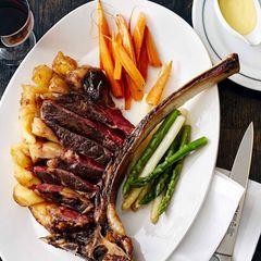 Tomahawk-Steak mit Gewürzmöhren und Spargel
