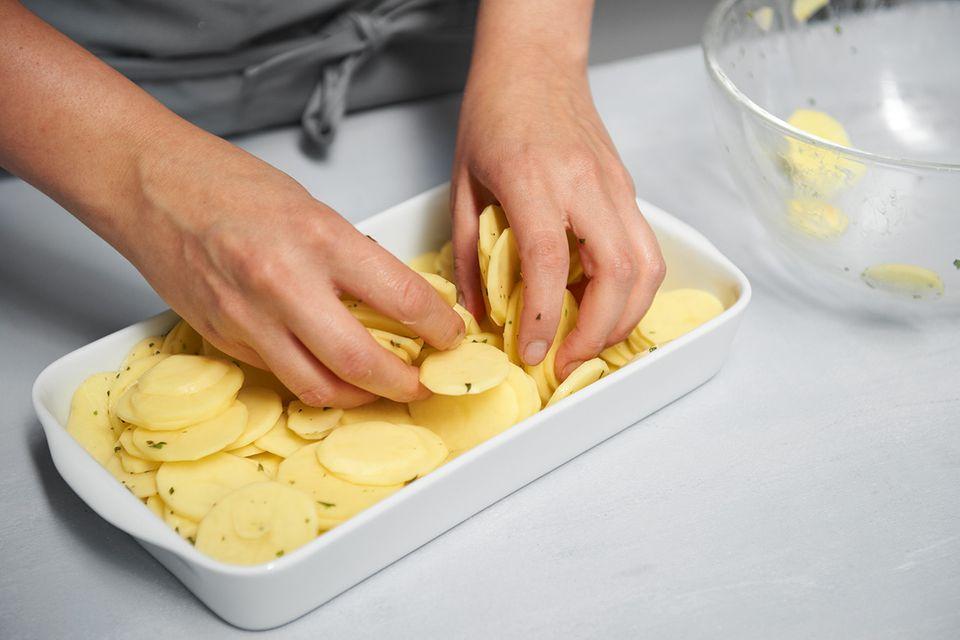 Kartoffelscheiben in eine Auflaufform schichten