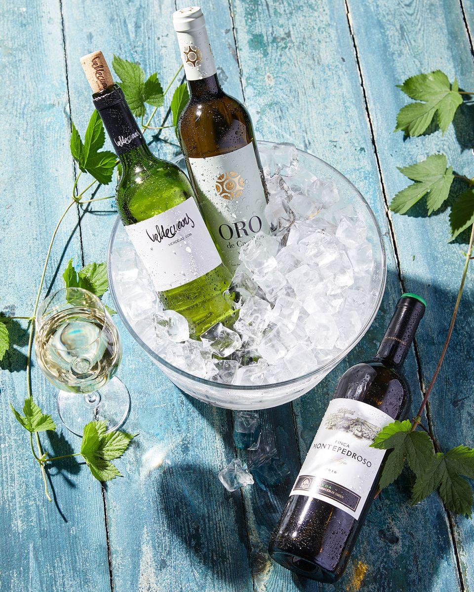 Weißwein Verdejo in Flaschen in einem Kühler mit Eiswürfeln und Weißwein im Glas