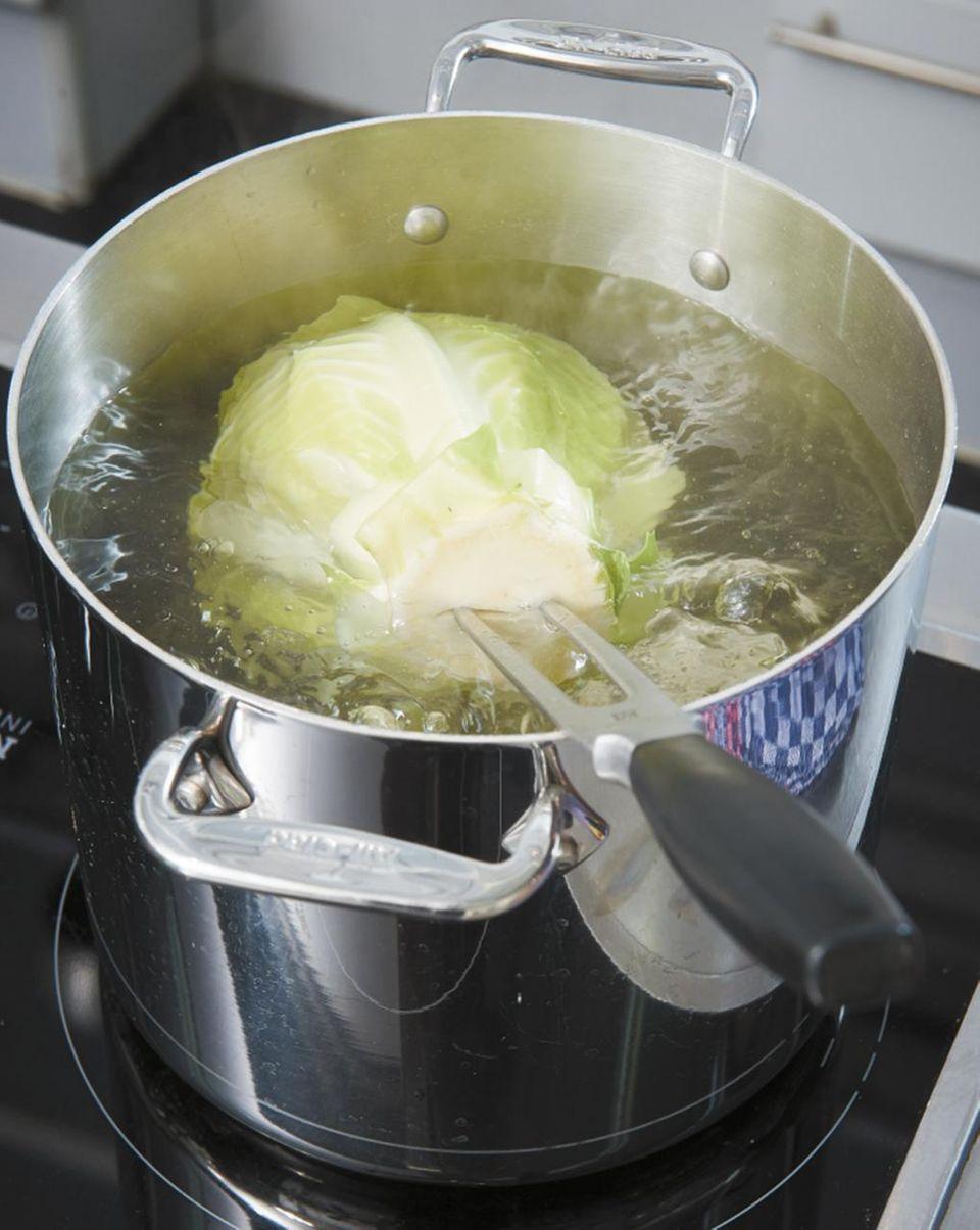 Weisskohl im kochenden Wasser im Topf mit einer Fleischgabel
