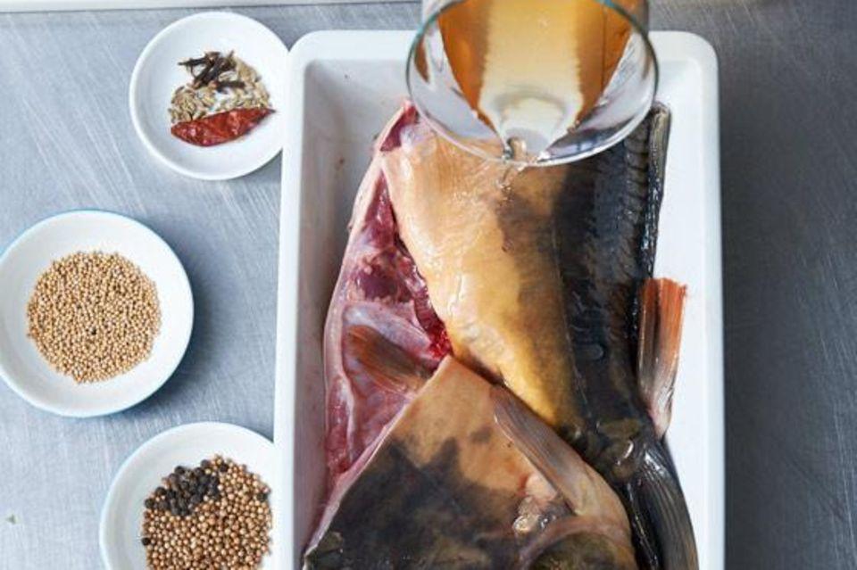 Karpfenstücke in einer Arbeitsschale mit Weißweinessig begießen