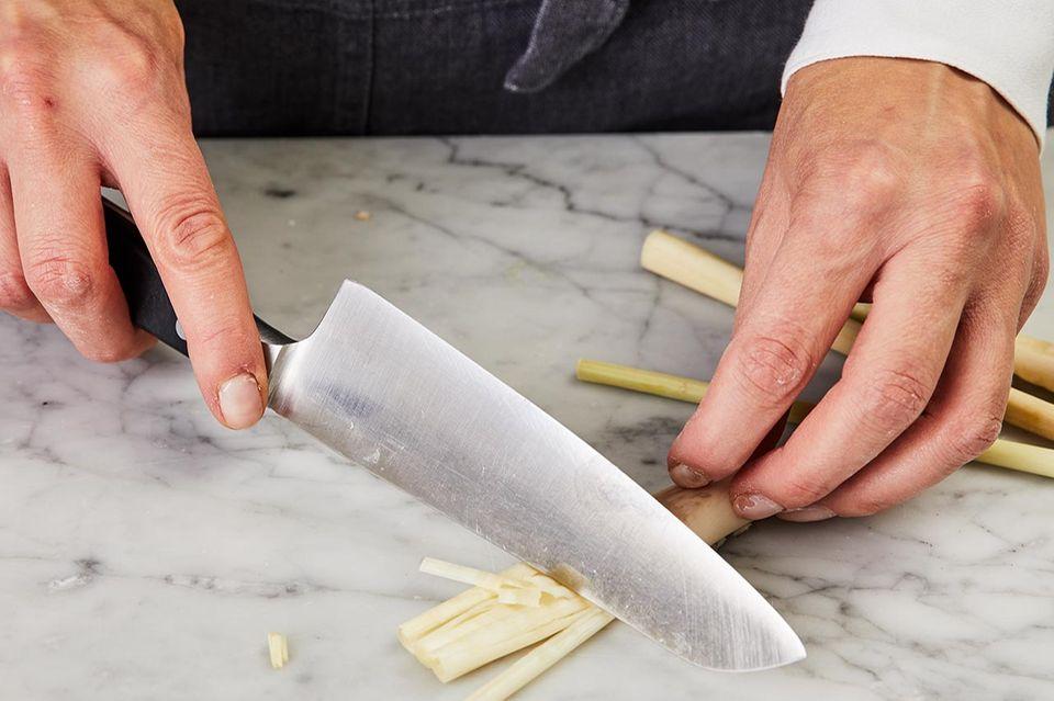 Mit einem Messerrücken das halbierte Zitronengras faserig geschlagen