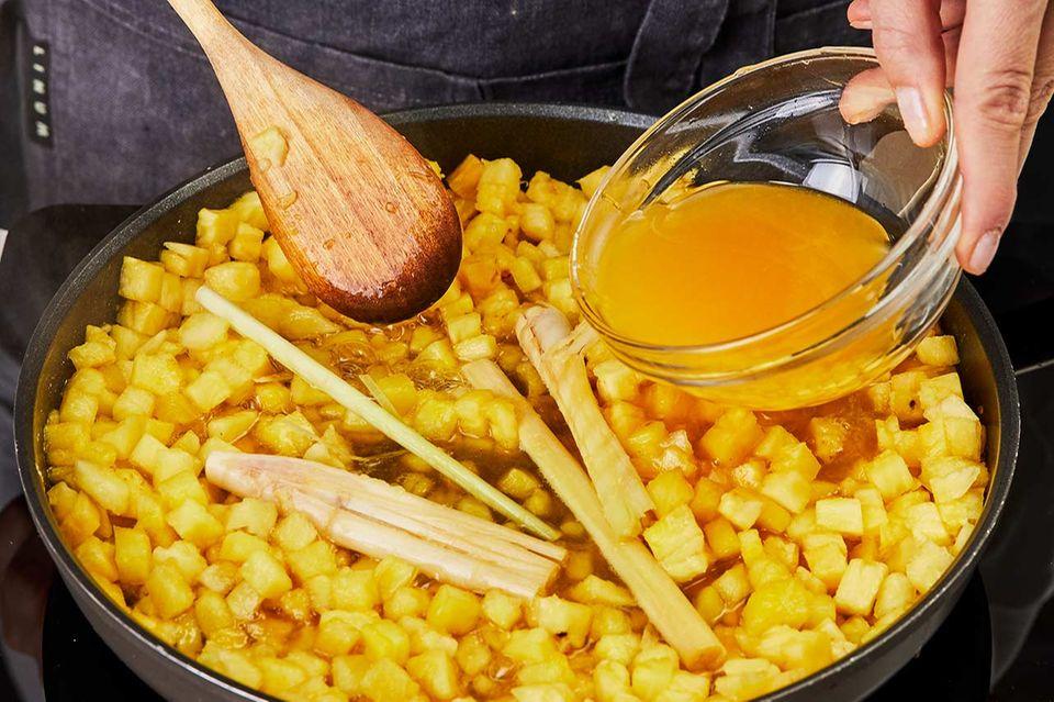 Ingwer, Zitronengras und Orangensaft zur Ananas geben und aufkochen