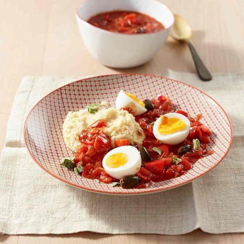 Teller mit cremiger Polenta und Eiern in Tomatensauce