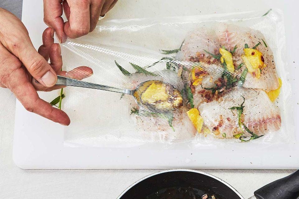 Vakuumbeutel mit Fisch und Kräutern befüllen