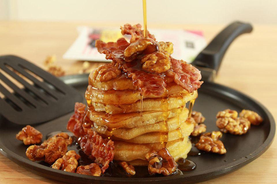 Frisch gebackene Pancakes mit Sirup, Nüssen und Bacon
