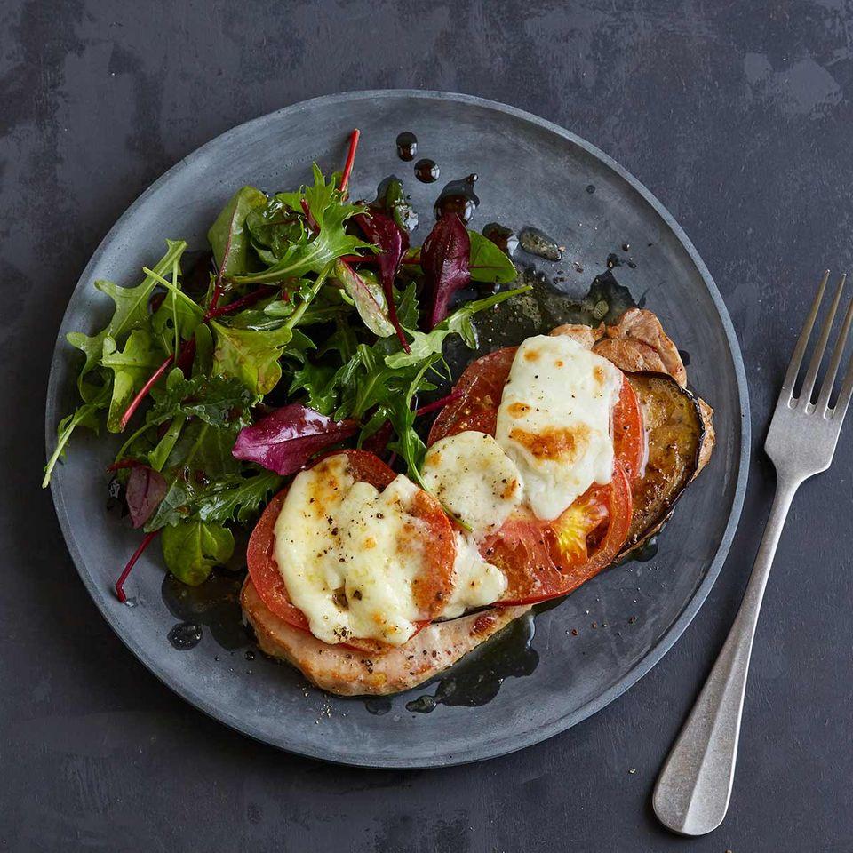 Überbackene Schnitzel mit Tomate, Mozzarella und Salat