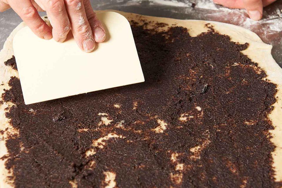 Zubereitung gefüllte Hefeschnecken: Teig mit Mohnmasse bestreichen