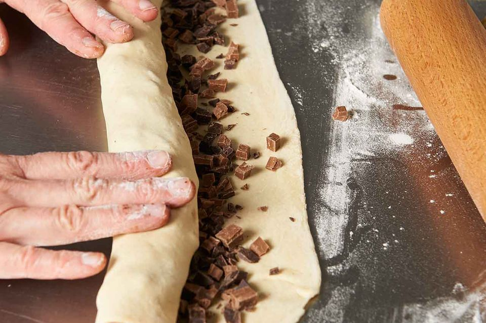 Zubereitung gefüllte Hefeschnecken: Teig mit Schokolade bestreuen und rollen