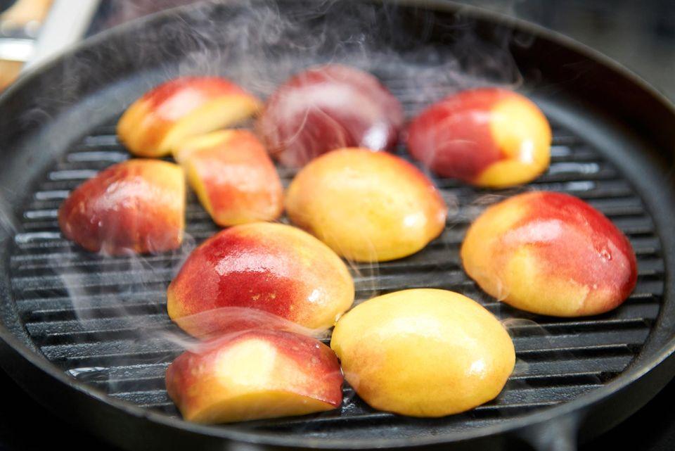 Pfirsiche auf einer Grillpfanne
