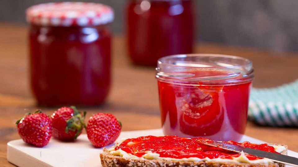 Erdbeermarmelade mit Vanille im Glas und auf dem Brot