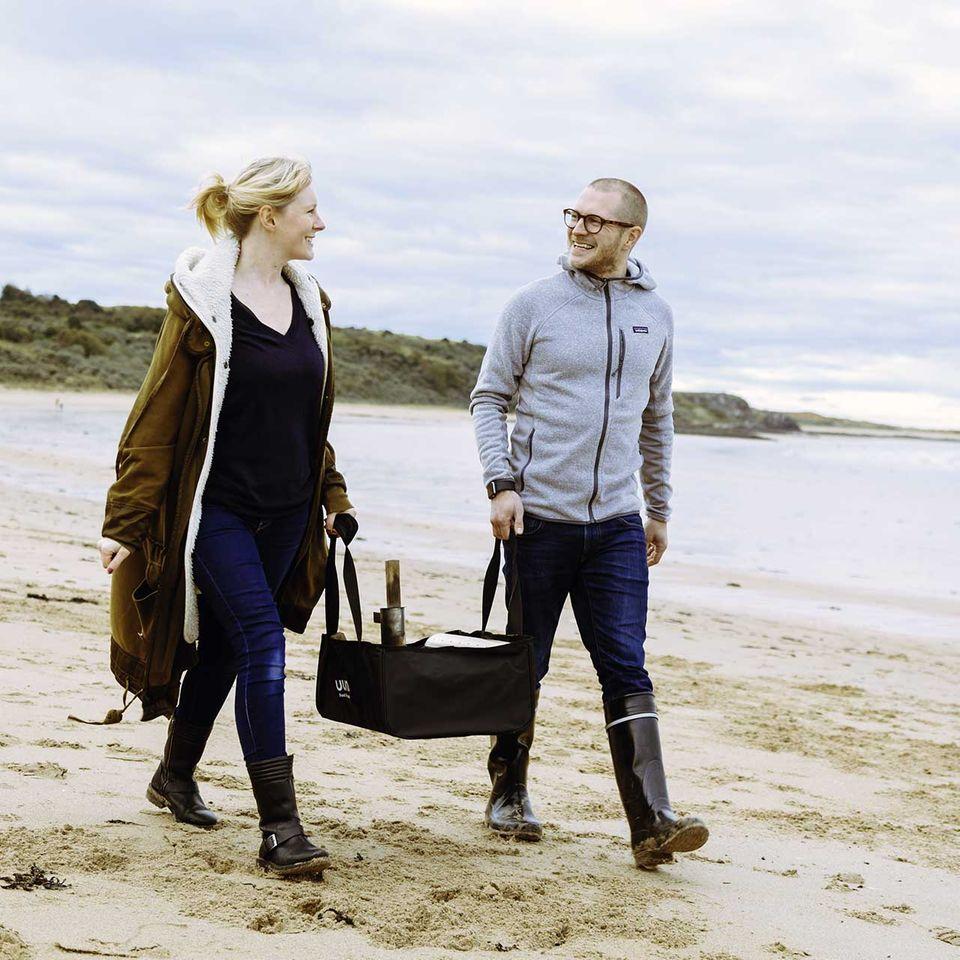 Darina und Kristian von Ooni am Strand mit einem Pizzaofen