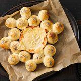 Kleine Brötchen um einen Ofenkäse arrangiert