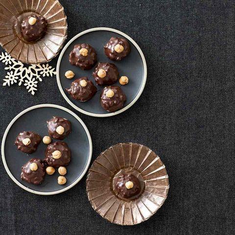 Kleine Kugeln mit Schokolade überzogen und einer Haselnuss on top