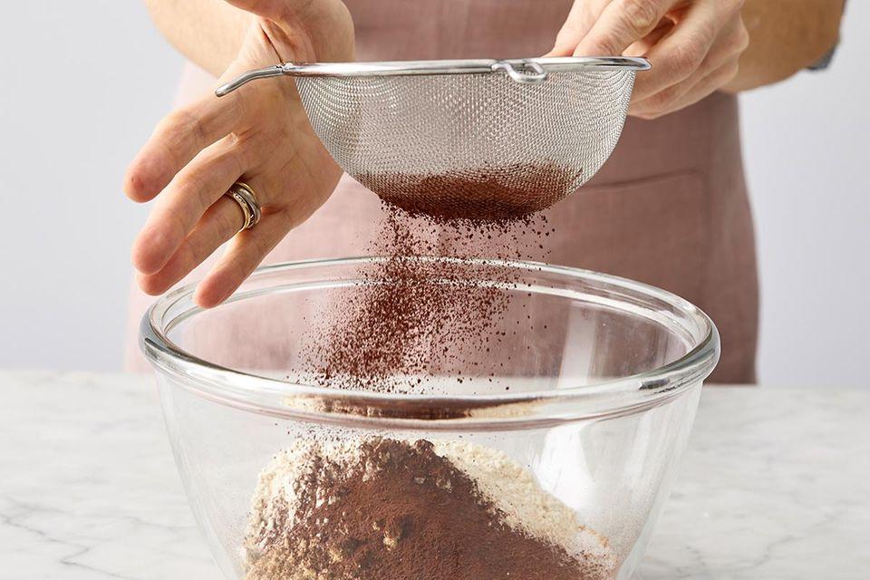 Kakaopulver über die Zutaten sieben