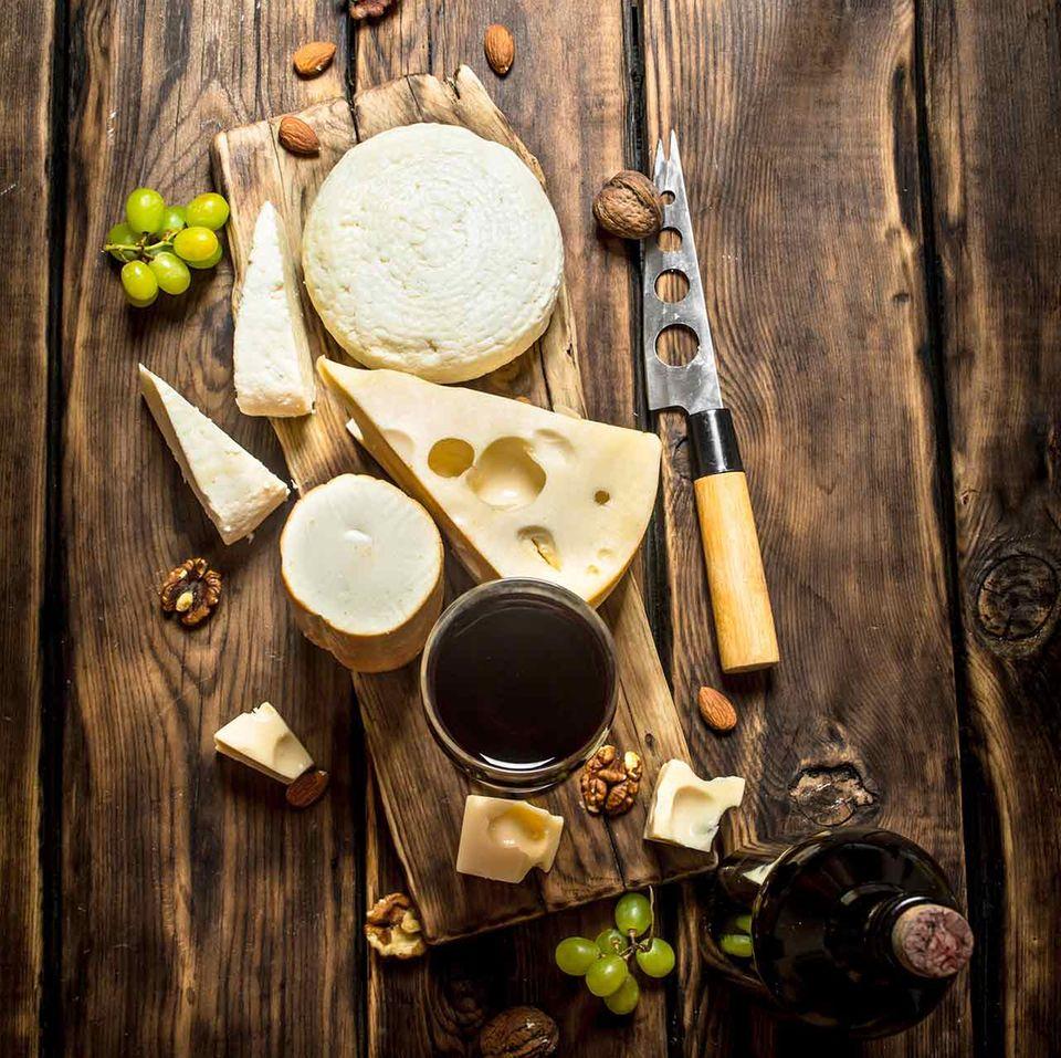 Rotweinglas mit verschiedenen Käsesorten auf Holztisch