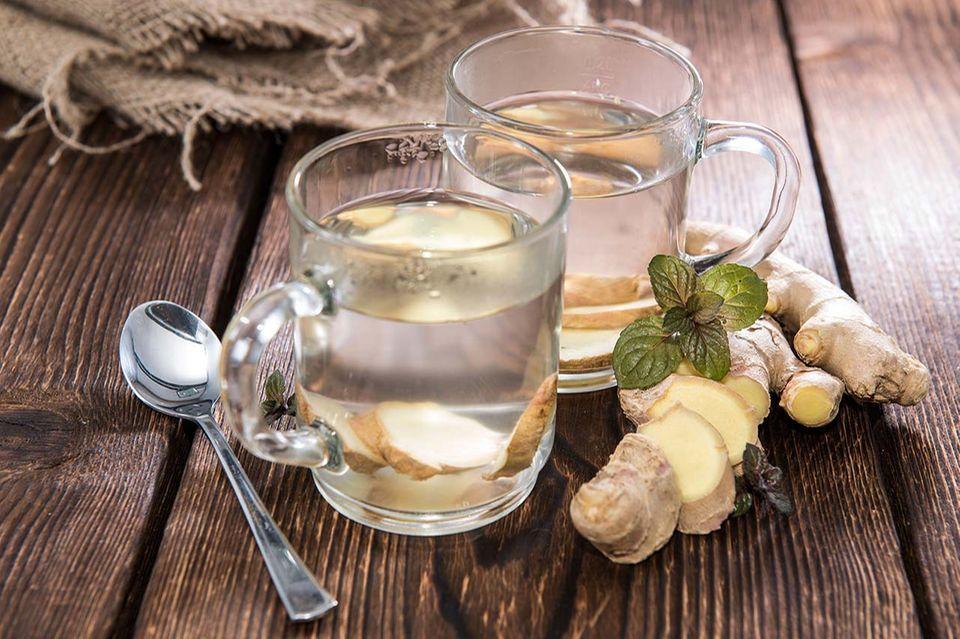 Ingwertee in Glastasse mit frischem Ingwer auf Tisch