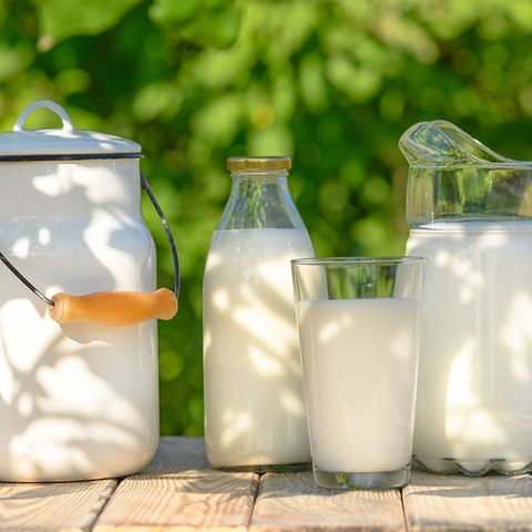 Milch in Krug, Glas und Flasche auf Holztische