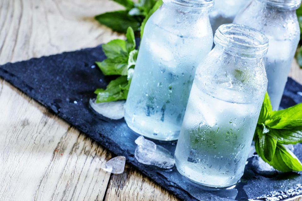 kaltes Wasser in Glasflasche auf schwarzem Brett