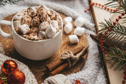Tasse mit Marshmallows mit Weihnachtsdeko auf Tisch