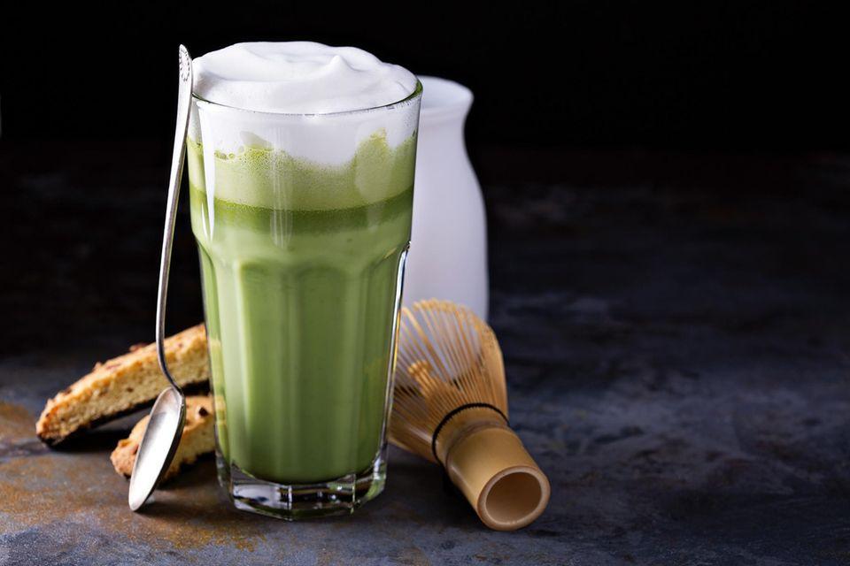 Matcha Latte im Glas mit Bambusbesen