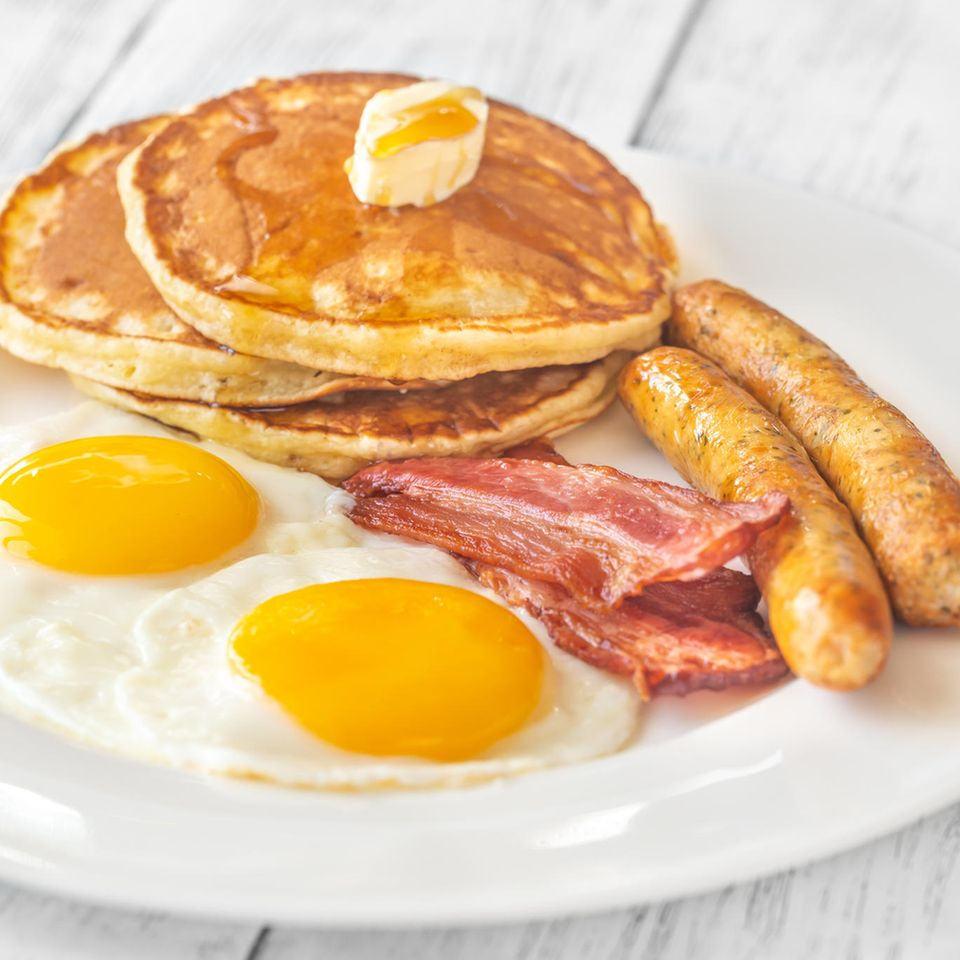 Amerikanisches Frühstück mit Ei, Pancakes, Würstchen und Speck