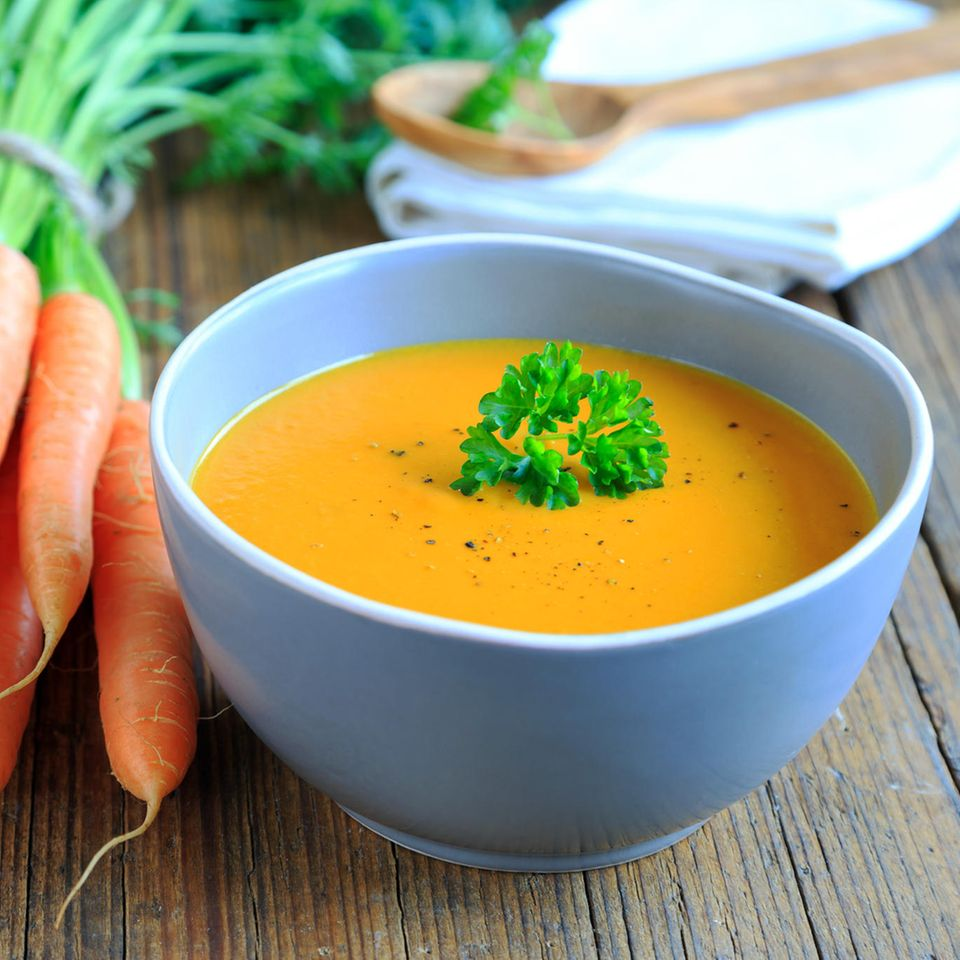 Karottensuppe im Teller und Karotten daneben