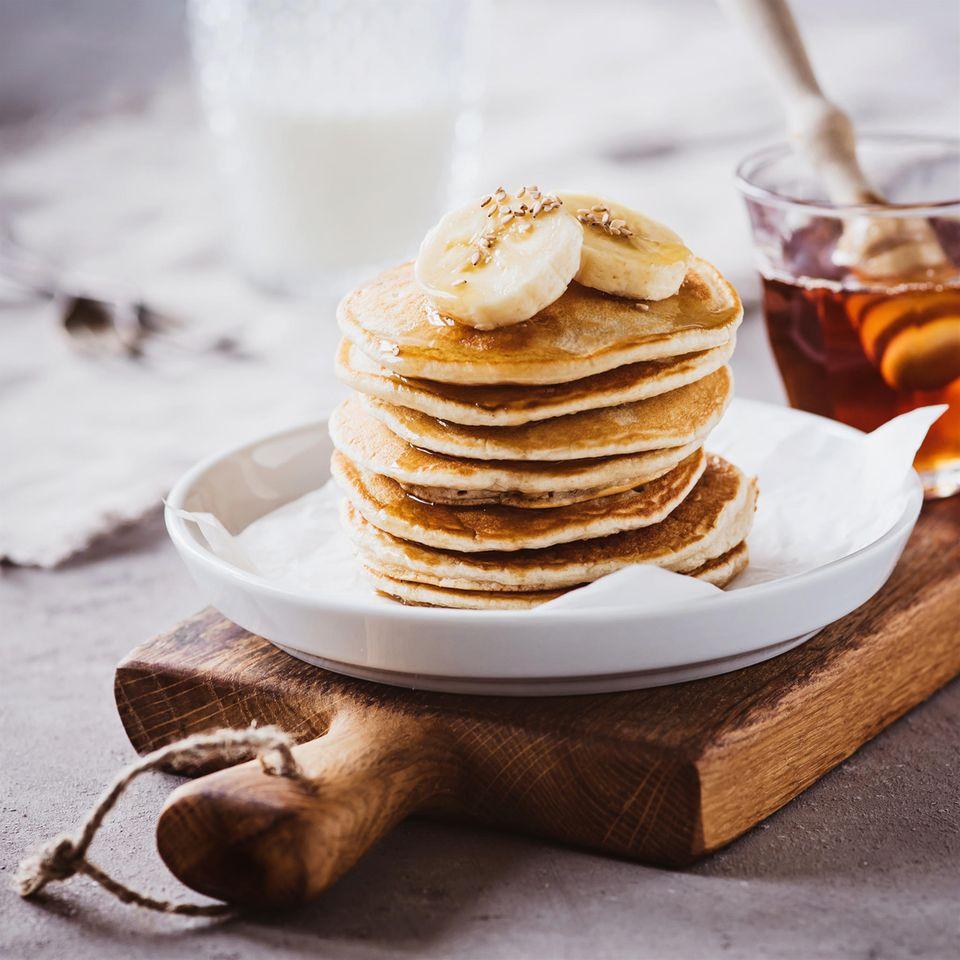 gesunde Pancakes aufeinander gestapelt mit Banane on Top auf weißem Teller
