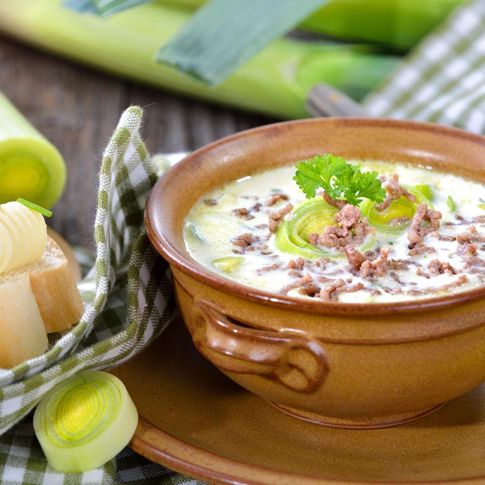 Käse-Lauch-Suppe in brauner Suppenschüssel mit Butterbaguette