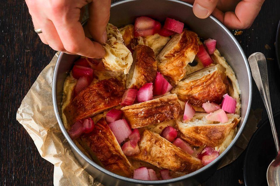 Croissants und Rharaberstücke auf den Teig geben