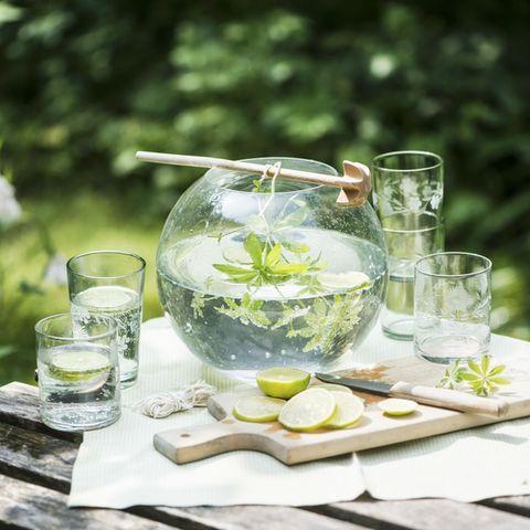 Maibowle im Gefäß im Garten