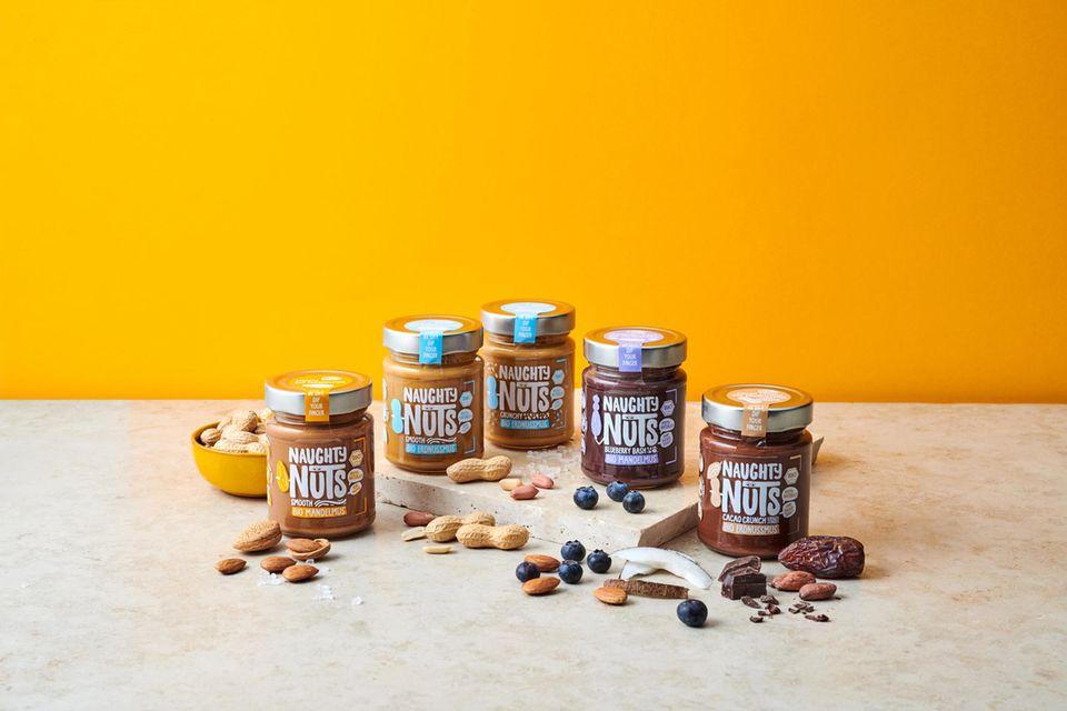 Nussmus-Sortiment von Naughty Nuts vor gelber Wand