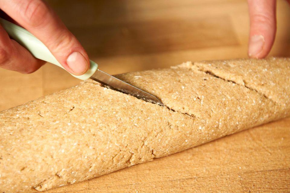 Die Baguettes auf ein mit Backpapier belegtes Blech geben und mehrmals schräg einschneiden