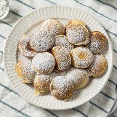 Einfach unwiderstehlich: original holländische Poffertjes – serviert mit einem Stück Butter und viel Puderzucker.