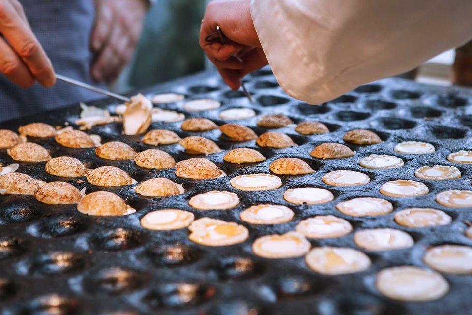 Auf Jahrmärkten werden Poffertjes in Profi-Eisen zubereitet, damit eine große Menge Poffertjes gleichzeitig gebacken werden kann.